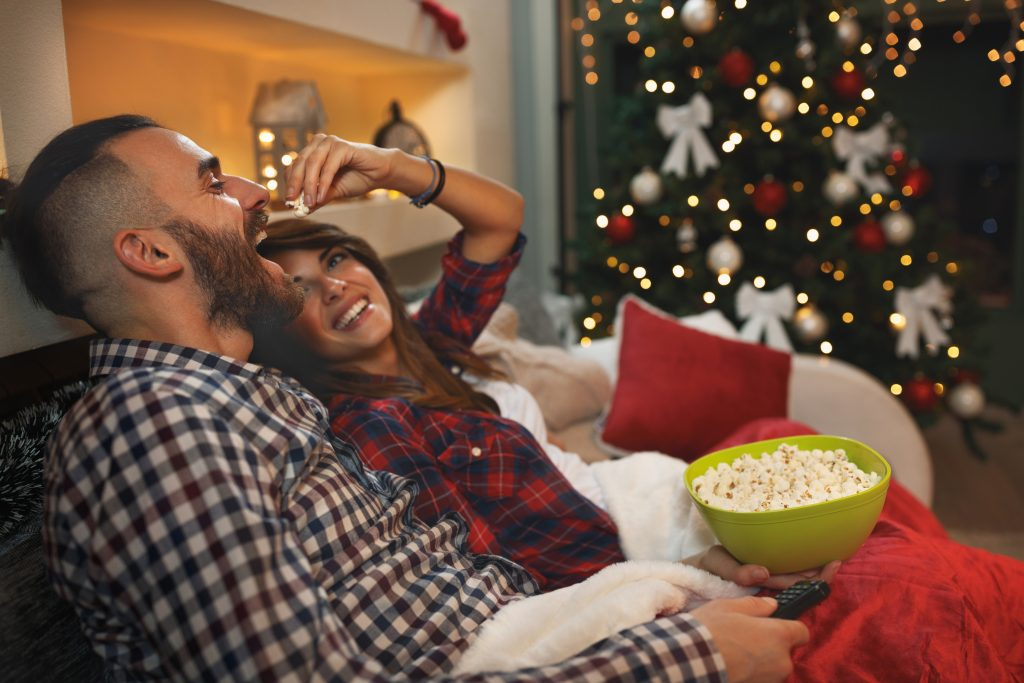 couple having fun watching holiday movies eating popcorn