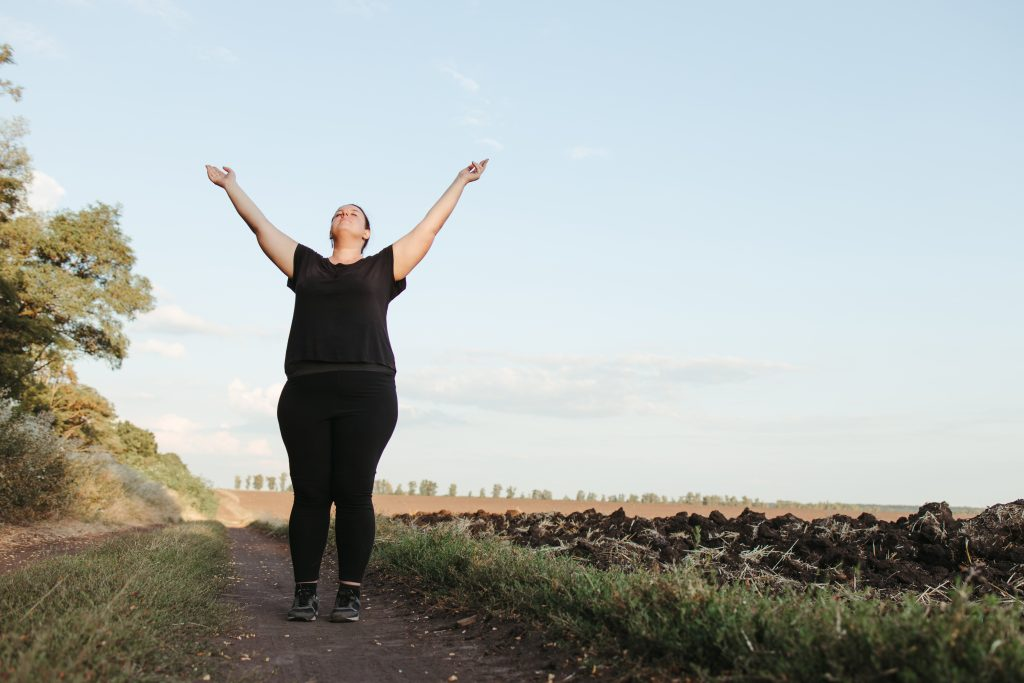Body positive, freedom, high self esteem, confidence, happiness, inspiration, success, positive affirmation. Overweight woman celebrating rising hands to the sky
